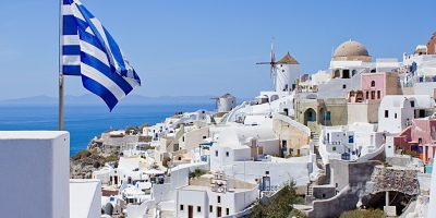 Legendary Mill Santorini in Greece on the background of the flag of Greece